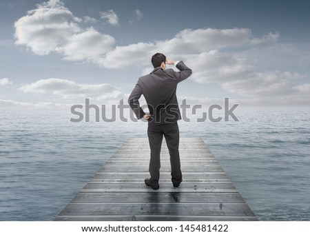 Businessman standing on a bridge and looking at the sea