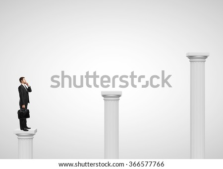 businessman standing on a column and talking on phone - stock photo