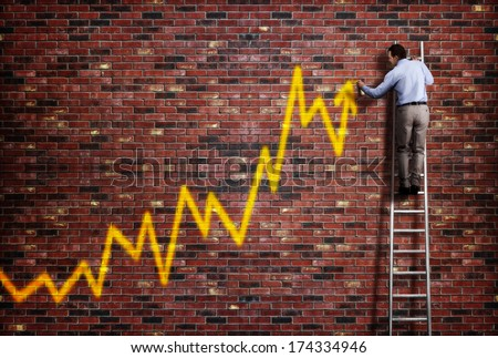 Businessman standing on a ladder and drawing a graph with positive trend in graffiti style yellow spray paint - stock photo