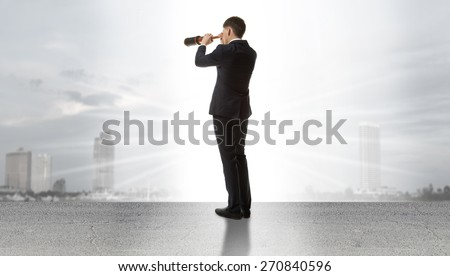 Businessman standing on a on road and looking through a telescope at city - stock photo