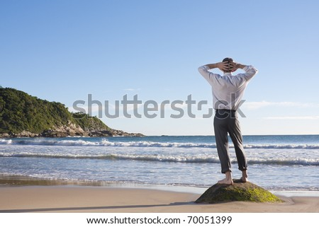 Businessman standing on a rock at the sea - stock photo