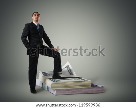 Businessman standing on a stack of dollars - stock photo