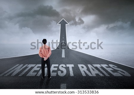 Businessman standing on an asphalt road turning into an ascending arrow with interest rates words on it  - stock photo