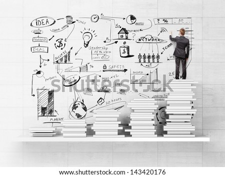 businessman standing on books and drawing strategy - stock photo