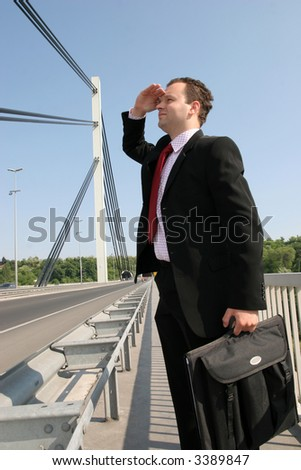 Businessman standing on bridge and looking - stock photo
