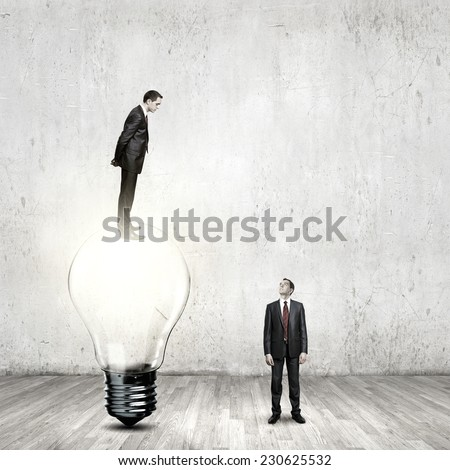 Businessman standing on bulb and looking down at colleague - stock photo
