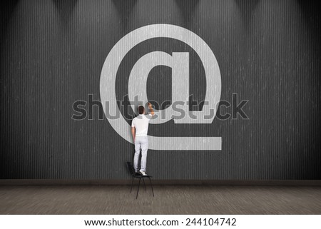businessman standing on chair and drawing email symbol - stock photo