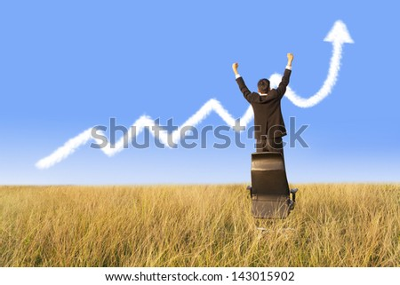 Businessman standing on chair with growing graph cloud - stock photo