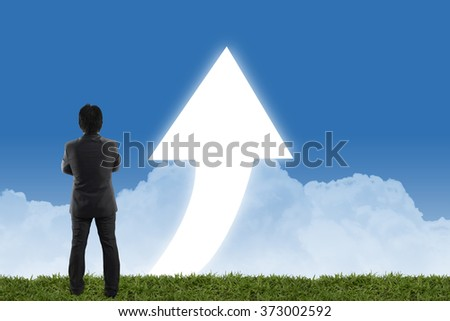 businessman standing on green grass in front of a big arrow pointing up with blue cloudy sky background. - stock photo