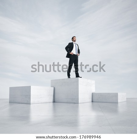 Businessman standing on highest cube - stock photo