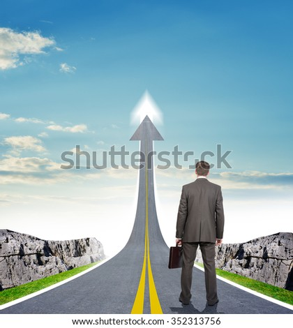Businessman standing on highway road going up in sky