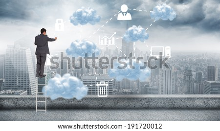 Businessman standing on ladder against cloud computing graphic with icons