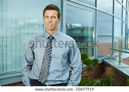 Businessman standing on office terrace outdoor, looking at camera, smiling. - stock photo