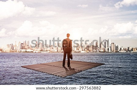 businessman standing on raft and looking to city - stock photo