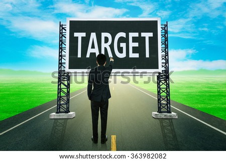 businessman standing on road and pointing with large sign of target (business concept) - stock photo