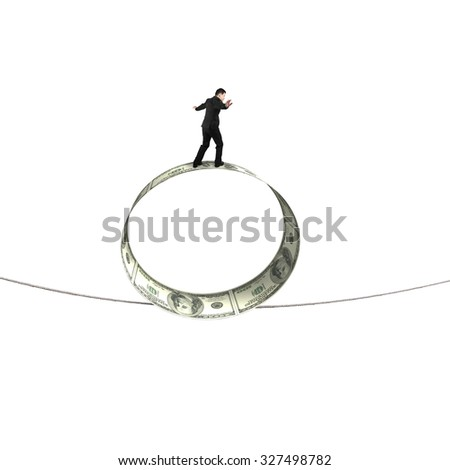 Businessman standing on roll of dollar bills balancing tightrope, isolated on white background. - stock photo