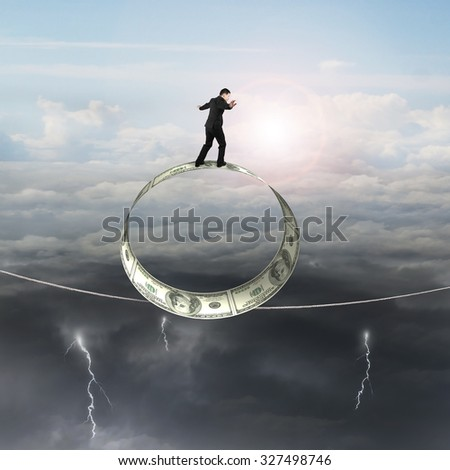 Businessman standing on roll of dollar bills balancing tightrope, with sky cloudscape background. - stock photo