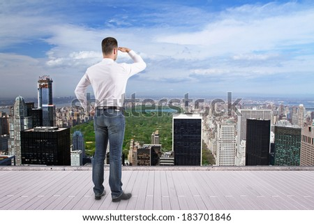 businessman standing on roof and looking at city