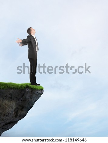 Businessman standing on the cliff - stock photo