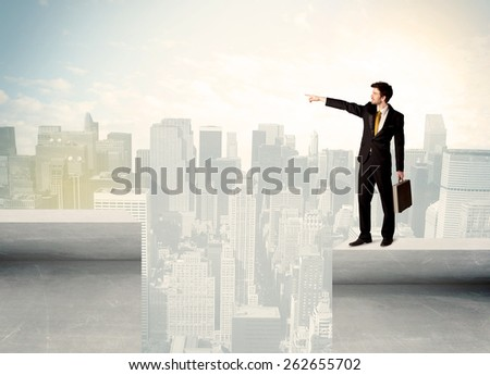Businessman standing on the edge of rooftop with city background