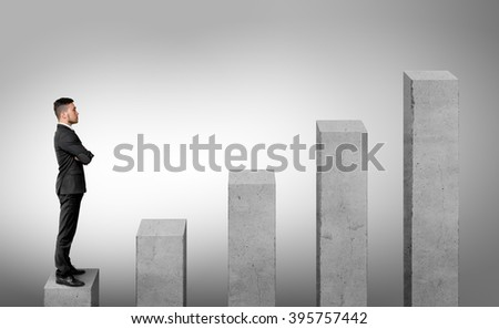 Businessman standing on the first of five columns with his arms folded.  - stock photo
