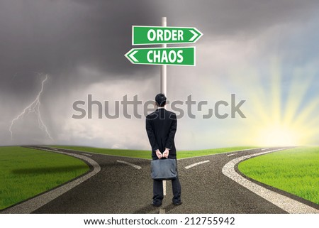 Businessman standing on the road looking at signpost of order and chaos - stock photo