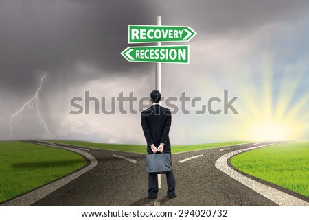 Businessman standing on the road while looking at the road sign guide to recession and recovery finance - stock photo