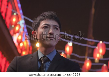 Businessman standing on the street, red lanterns on the background - stock photo