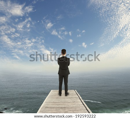 businessman standing on wooden pier and looking to sky