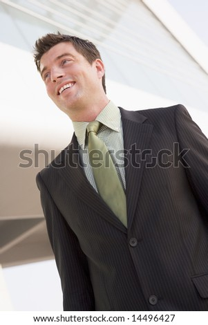 Businessman standing outdoors by building smiling