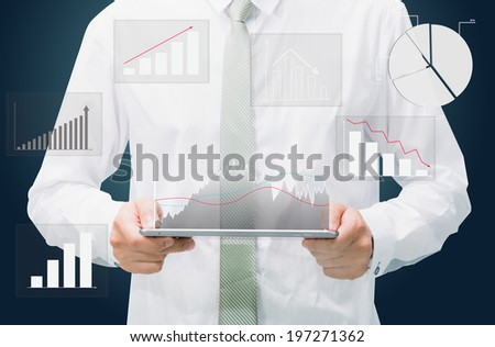 Businessman standing posture hand graph on tablet isolated on dark background - stock photo