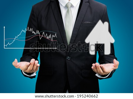 Businessman standing posture hand hold graph and house isolated on over blue background