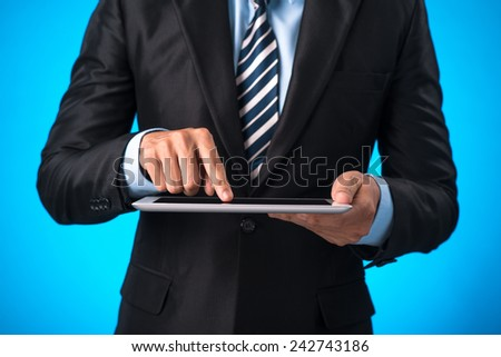 Businessman standing posture hand hold graph on tablet isolated on blue background. touch screen ,touch- tablet in hands - stock photo