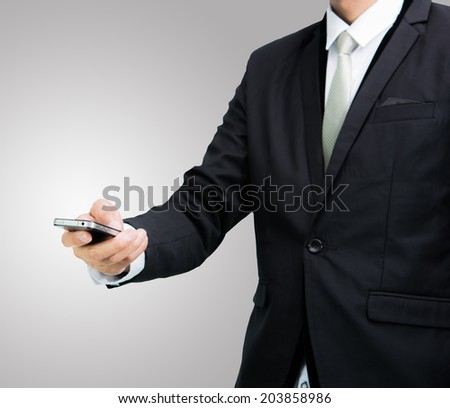 Businessman standing posture hand hold phone isolated on over gray background - stock photo