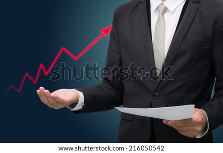 Businessman standing posture hand holding graph finance isolated on dark background - stock photo