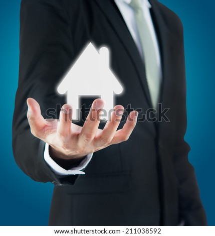 Businessman standing posture hand holding house icon on over blue background