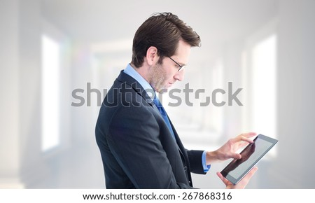Businessman standing while using a tablet pc against digitally generated room - stock photo