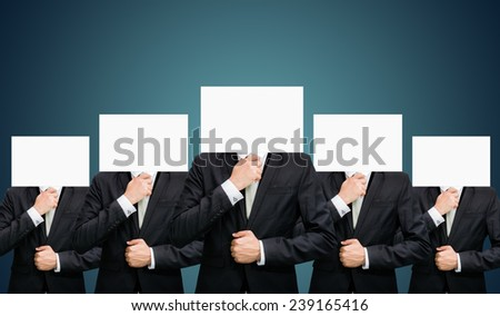 Businessman standing white paper face holding front of head on dark background - stock photo