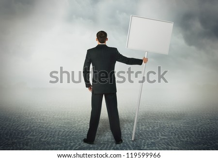 Businessman standing with a placard in his hand - stock photo