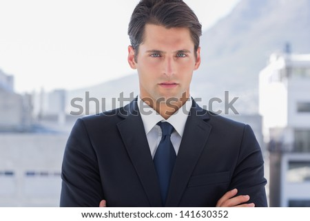 Businessman standing with arms crossed in a bright office - stock photo