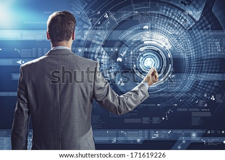 Businessman standing with back against media screen