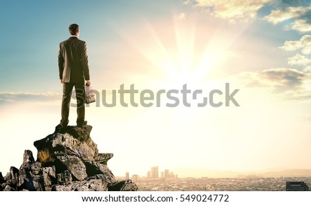 Businessman standing with back against morning city, panoramic view