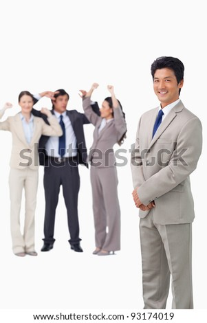 Businessman standing with cheering team behind him against a white background - stock photo