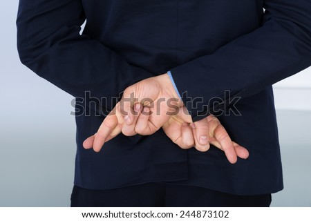 Businessman Standing With Crossed Finger Behind His Back - stock photo