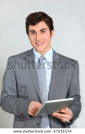 Businessman standing with electronic pad - stock photo