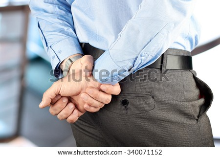 businessman  standing  with  hands behind his back.  - stock photo