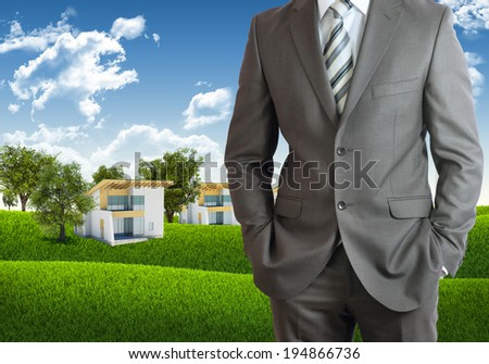 Businessman standing with hands in pockets. Blue sky, green grass and town as backdrop - stock photo