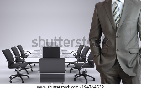 Businessman standing with hands in pockets. Conference table, chairs and laptops as backdrop - stock photo