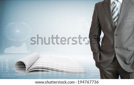 Businessman standing with hands in pockets. On background of the open book and high-tech graphs - stock photo