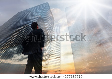 Businessman standing with hands on hips against low angle view of skyscrapers at sunset - stock photo